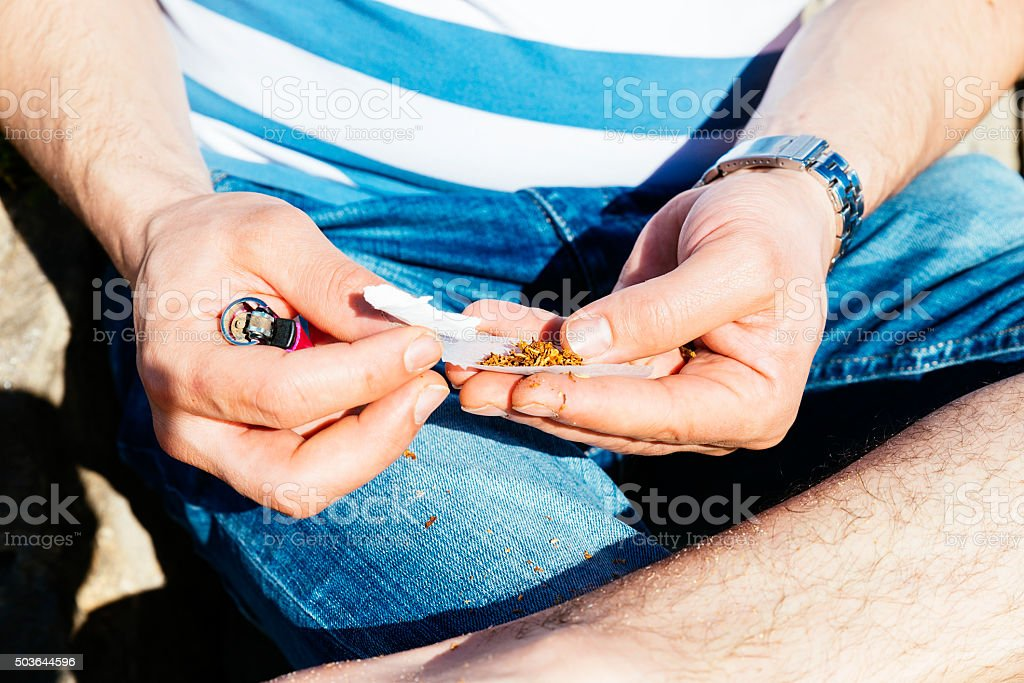 Hands rolling a cigarette with rolling tobacco stock photo