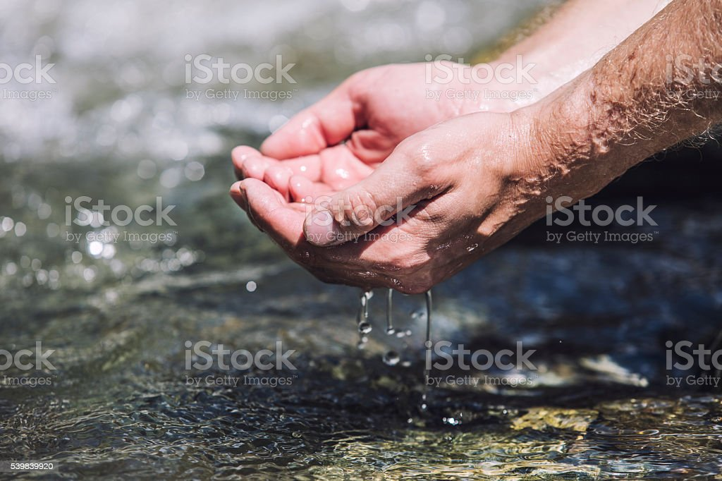 Hands sachibalaya clean water from the mountain bubbling stock photo