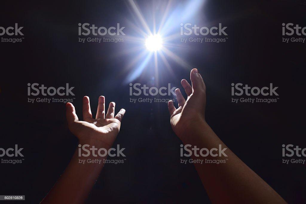 hands seeking light in the dark stock photo