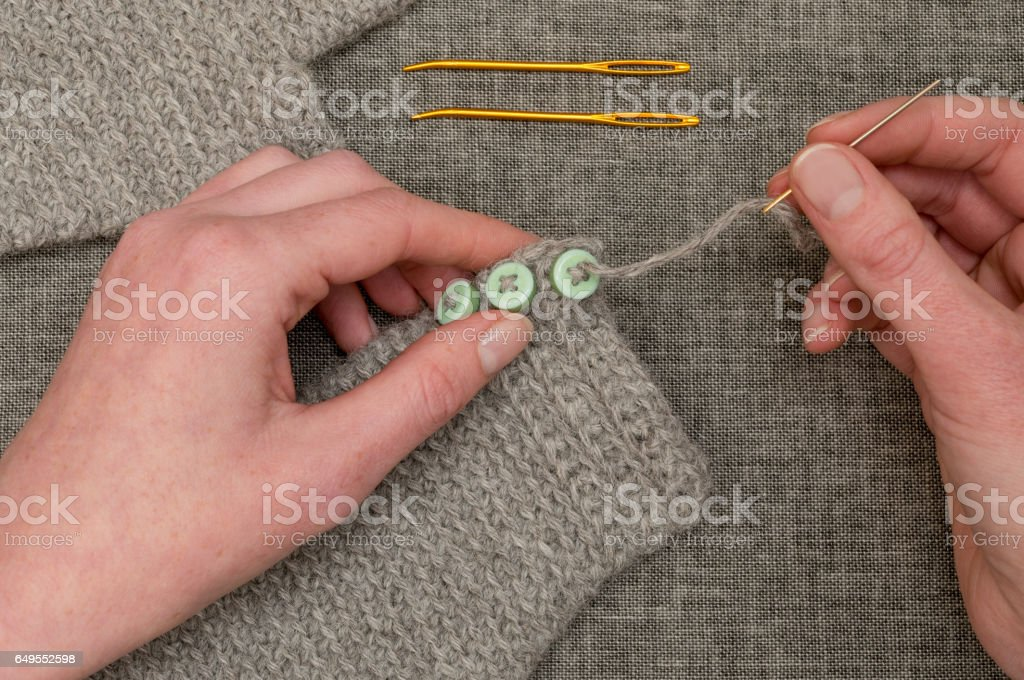 Hands Sewing Buttons onto Crocheted Gray Fabric stock photo