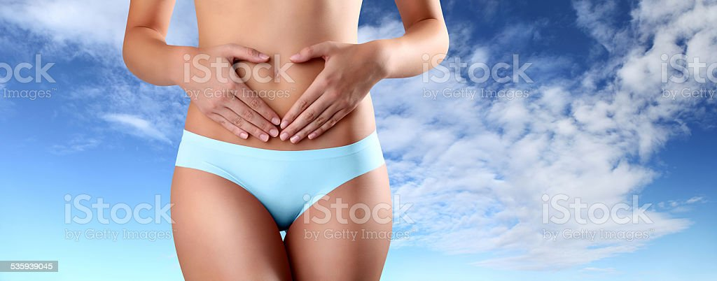 hands shape heart on the belly of woman stock photo