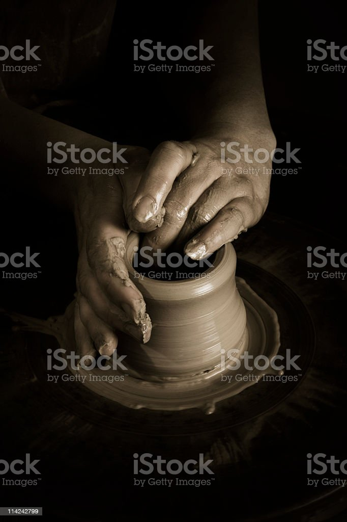 Hands shaping clay on a potters wheel in darkness stock photo