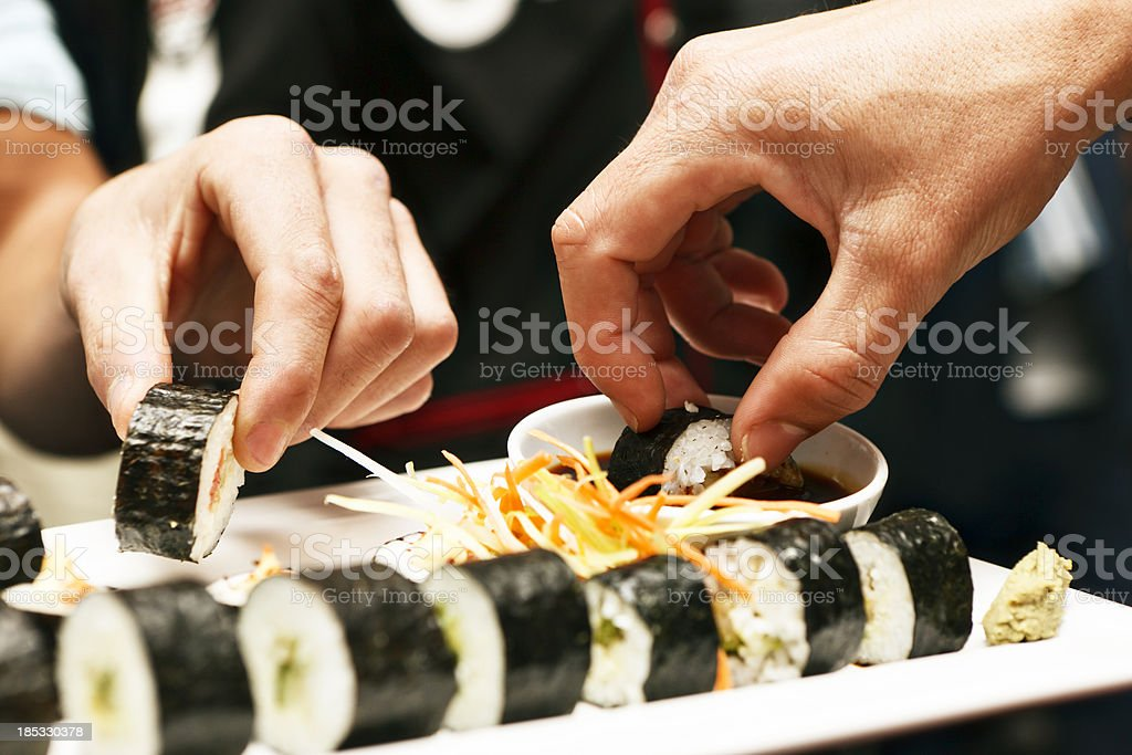 Hands sharing a sushi platter in Asian restaurant stock photo