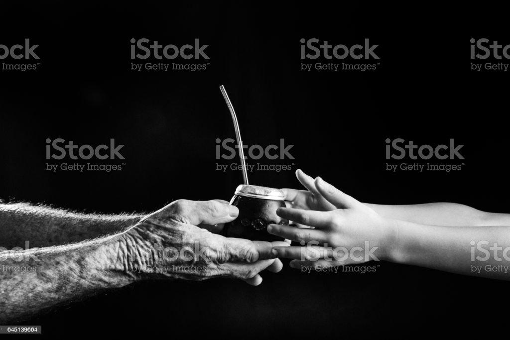 Hands sharing yerba mate drink stock photo