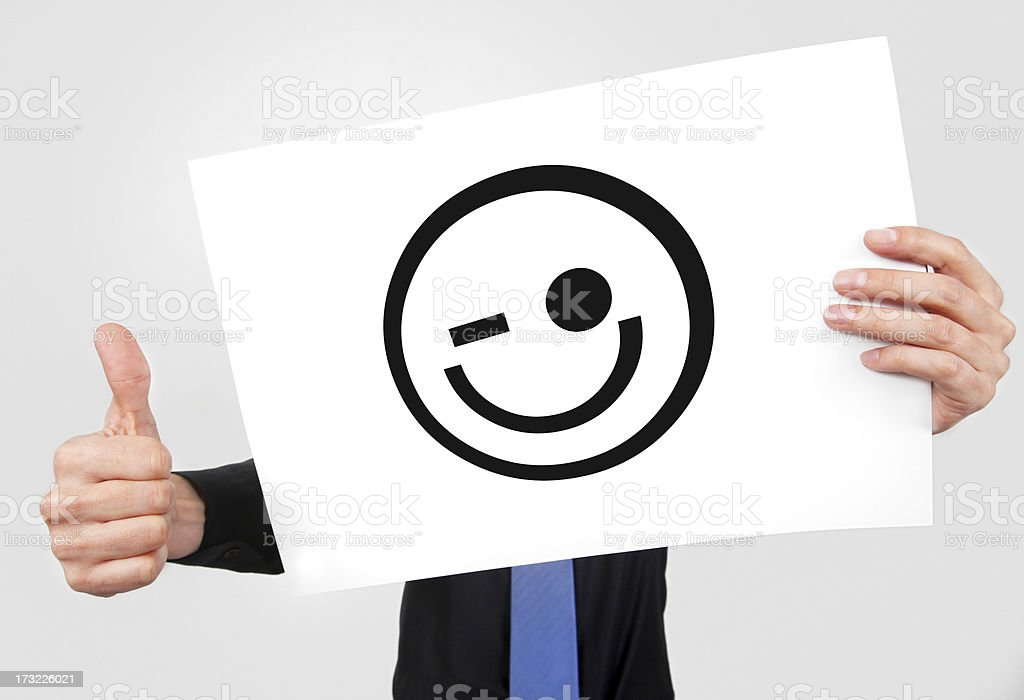 2 hands showing a smiley icon on a white paper & a thumb up royalty-free stock photo