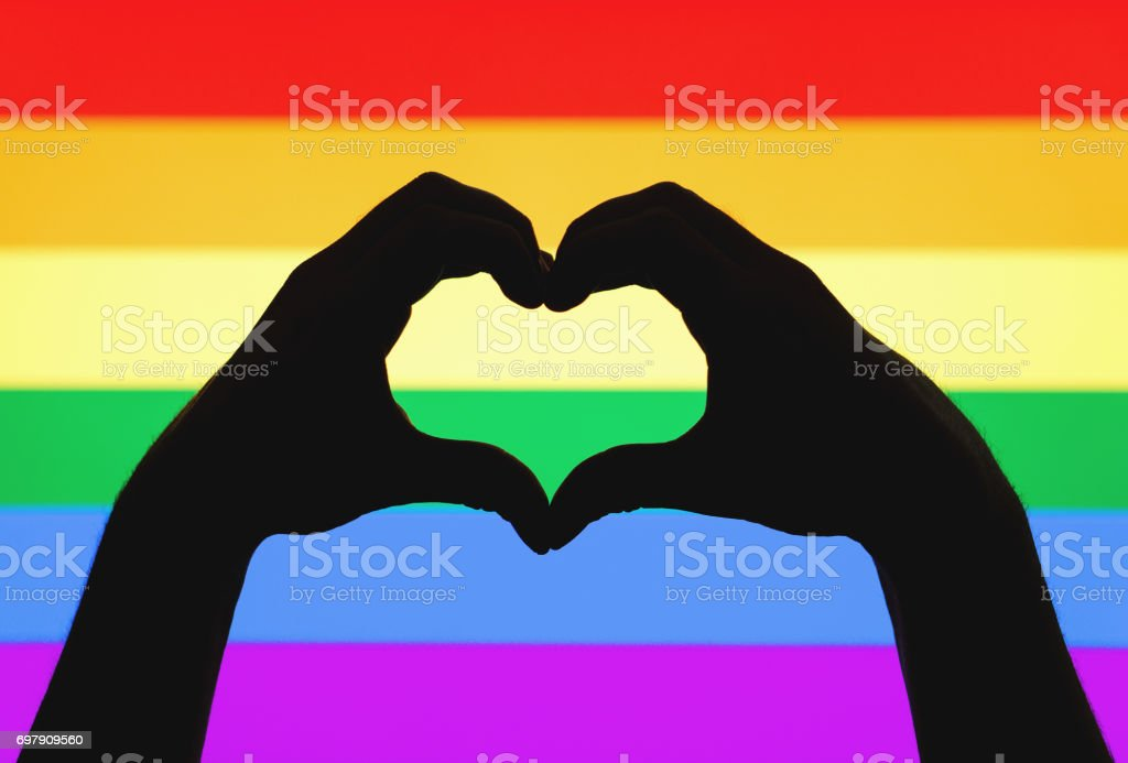 Hands showing heart sign on gay pride and LGBT rainbow flag. Sexual minority,  homosexuality and equal rights concept. Silhouette of love symbol on colorful background. stock photo
