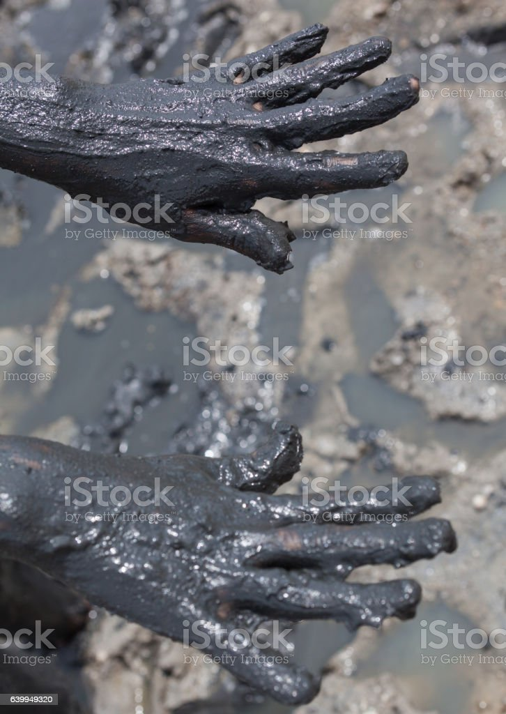 Hands smeared with black healing mud stock photo