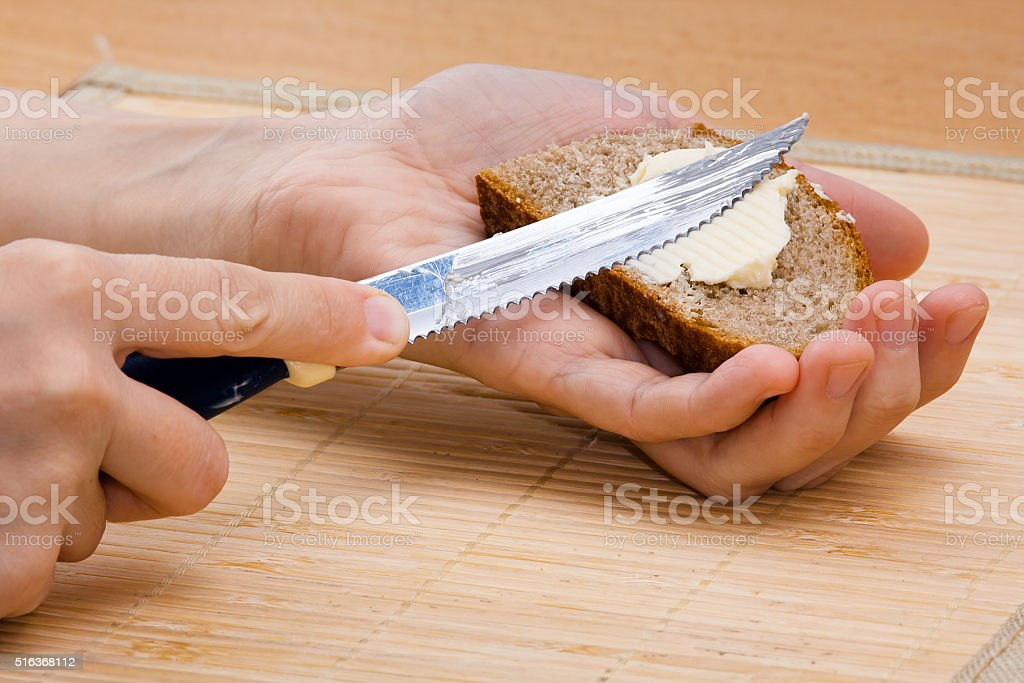 hands spreading butter on piece of rye bread, closeup stock photo