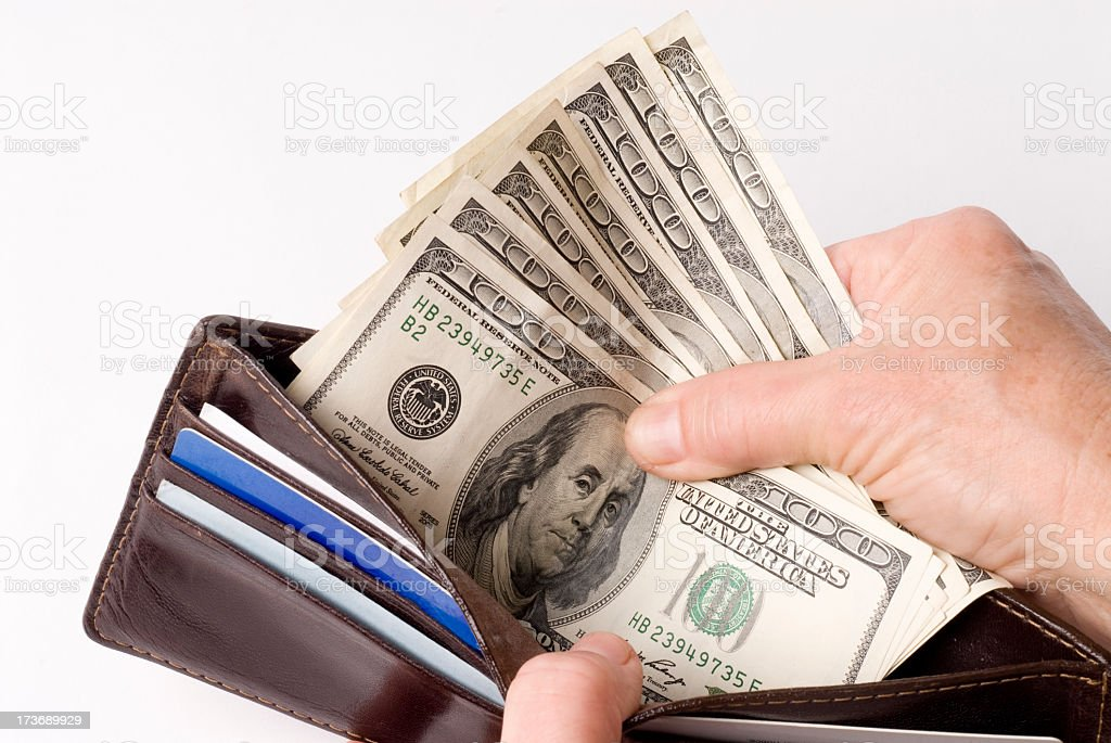 Hands spreading open a wallet, showing 5 100 dollar bills stock photo