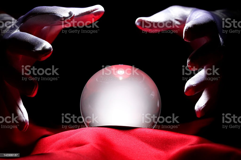 Hands surrounding a glowing crystal ball on red fabric stock photo