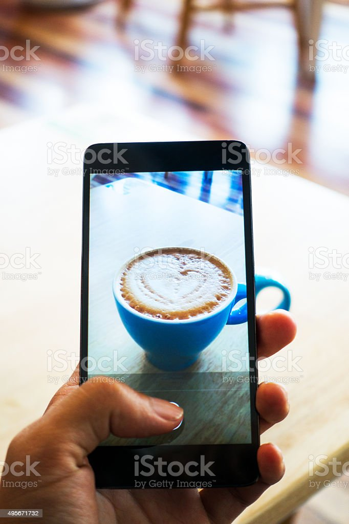Hands taking photo coffee with smartphone stock photo