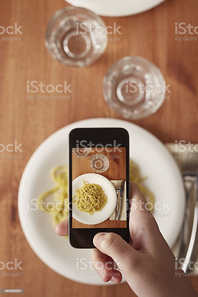 Hands taking photo of lunch with smartphone stock photo