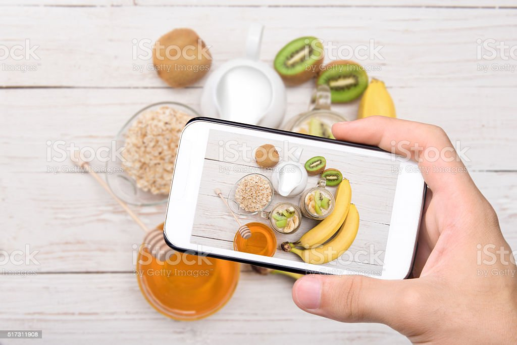 Hands taking photo smoothies with oatmeal with smartphone. stock photo