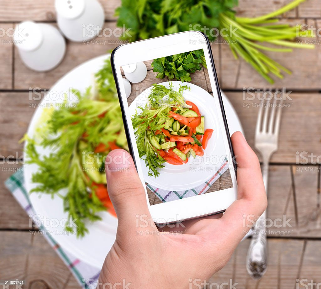 Hands taking photo vegetable salad with smartphone stock photo