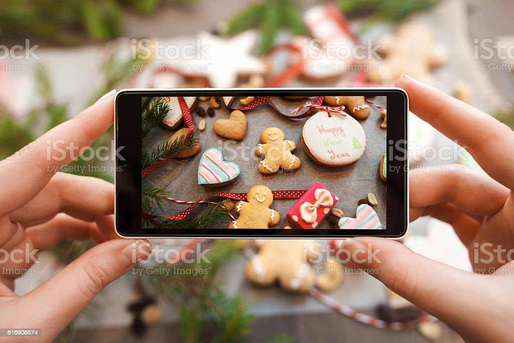 Hands taking picture of gingerbread cookies stock photo