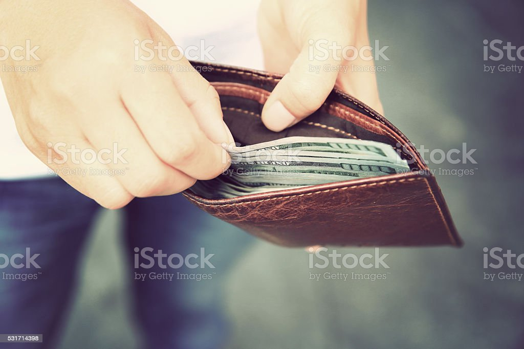 Hands taking  us dollars  out from wallet on the street stock photo