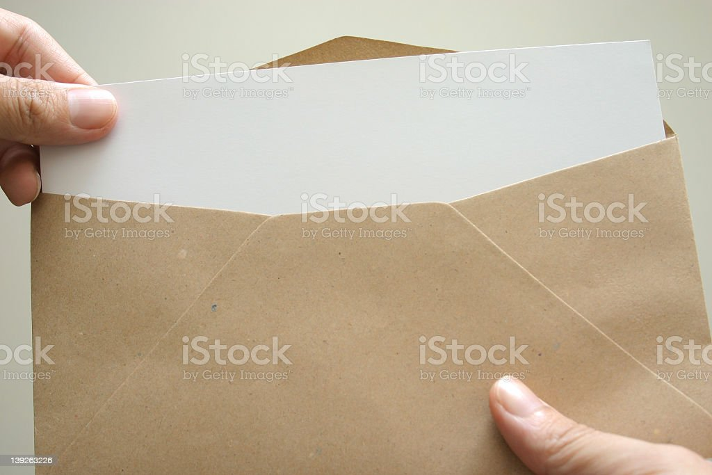 Hands taking white paper out of brown Manila envelope stock photo