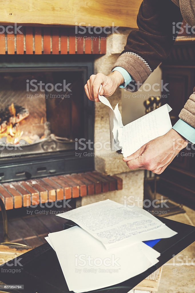 Hands tear sheets in bathrobe in front of burning fireplace stock photo