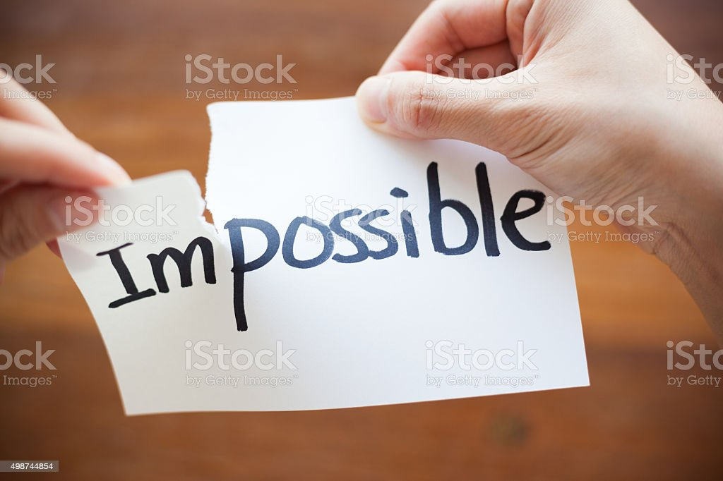 Hands Tearing Paper with the Words - Impossible become Possible stock photo