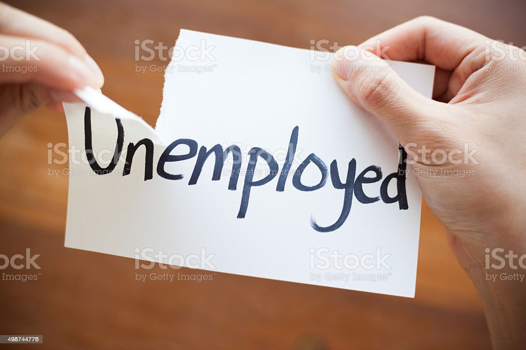 Hands Tearing Paper with the Words - Unemployed become Employed stock photo