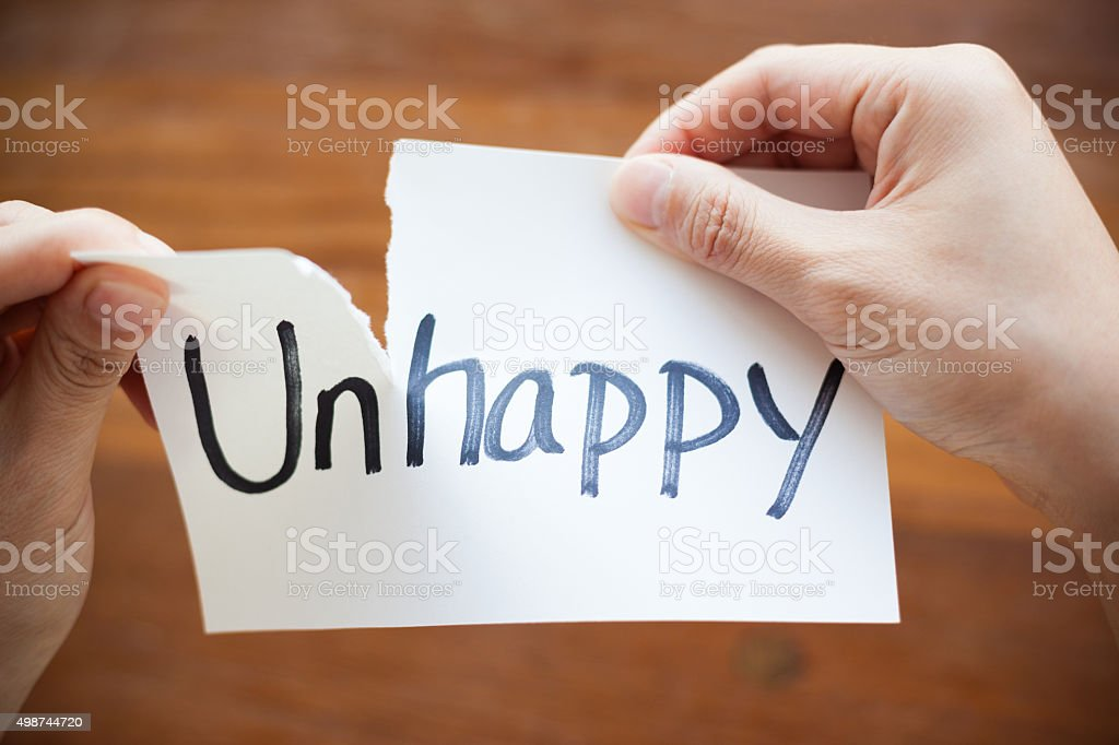 Hands Tearing Paper with the Words - Unhappy become Happy stock photo