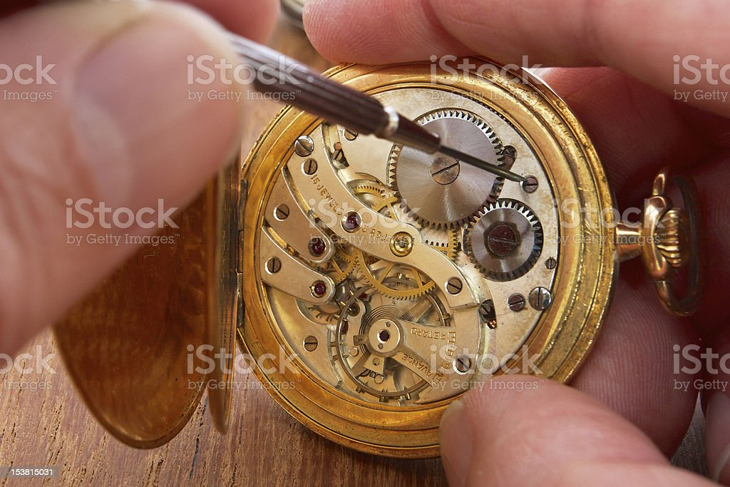 hands that repair an old pocket watch stock photo