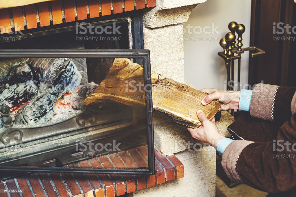 Hands thrust in bathrobe in large log fireplace stock photo