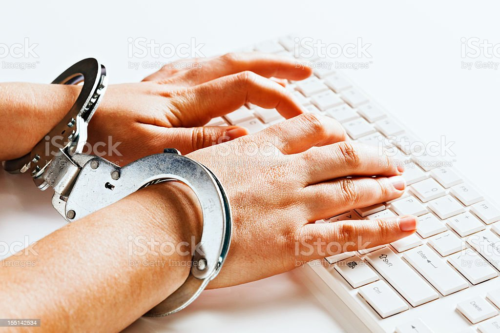 Hands tied unable to write freely on computer in handcuffs stock photo