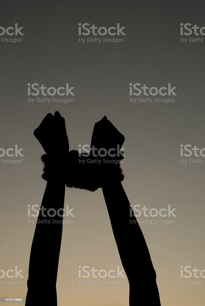 Hands tied up with rope against dark sky stock photo