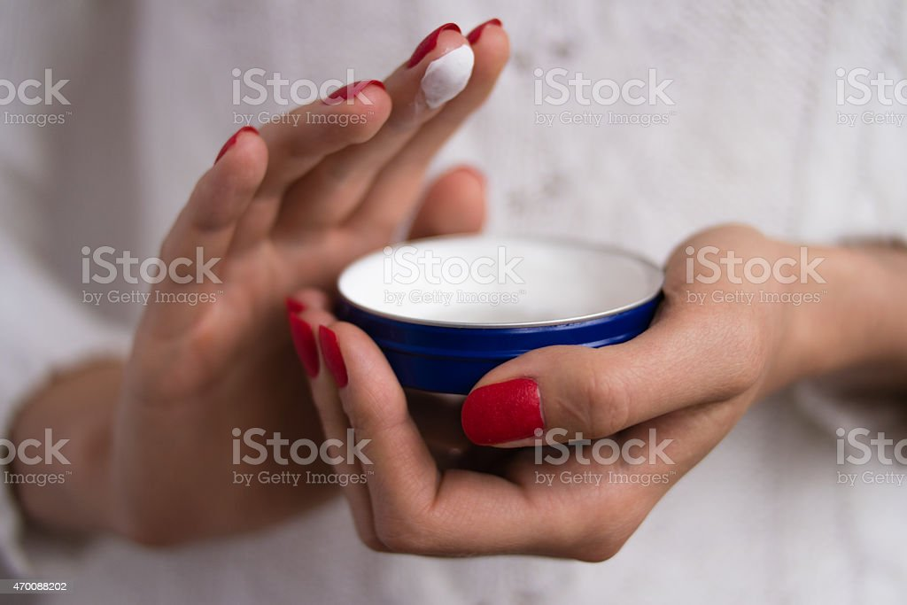 Hands to apply the cream out of the blue jar stock photo