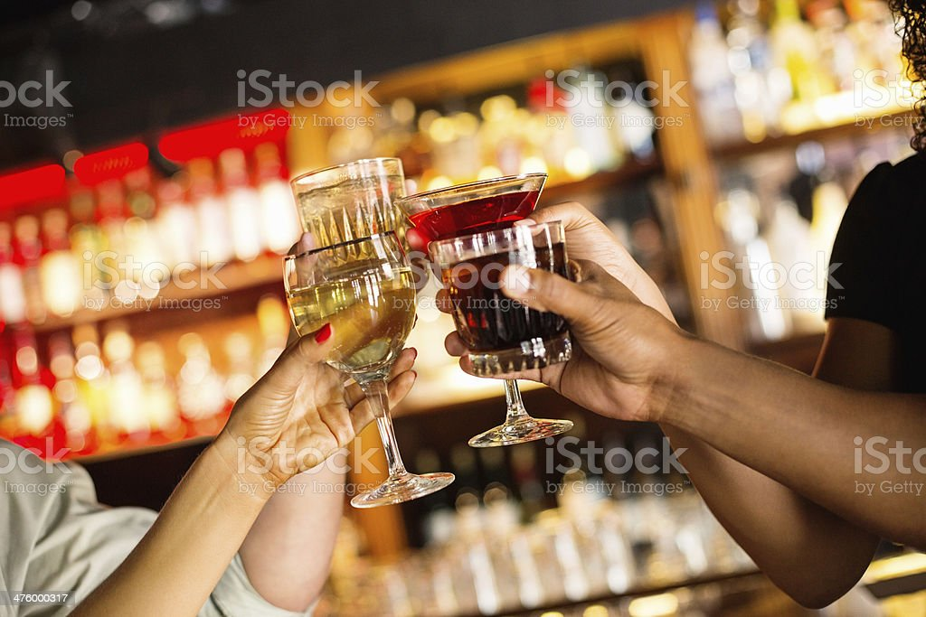 Hands Toasting Cocktail Glasses In Bar royalty-free stock photo