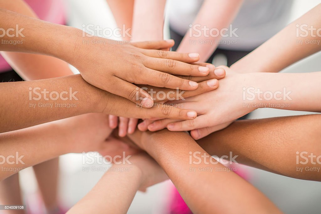 Hands Together in a Team Huddle stock photo