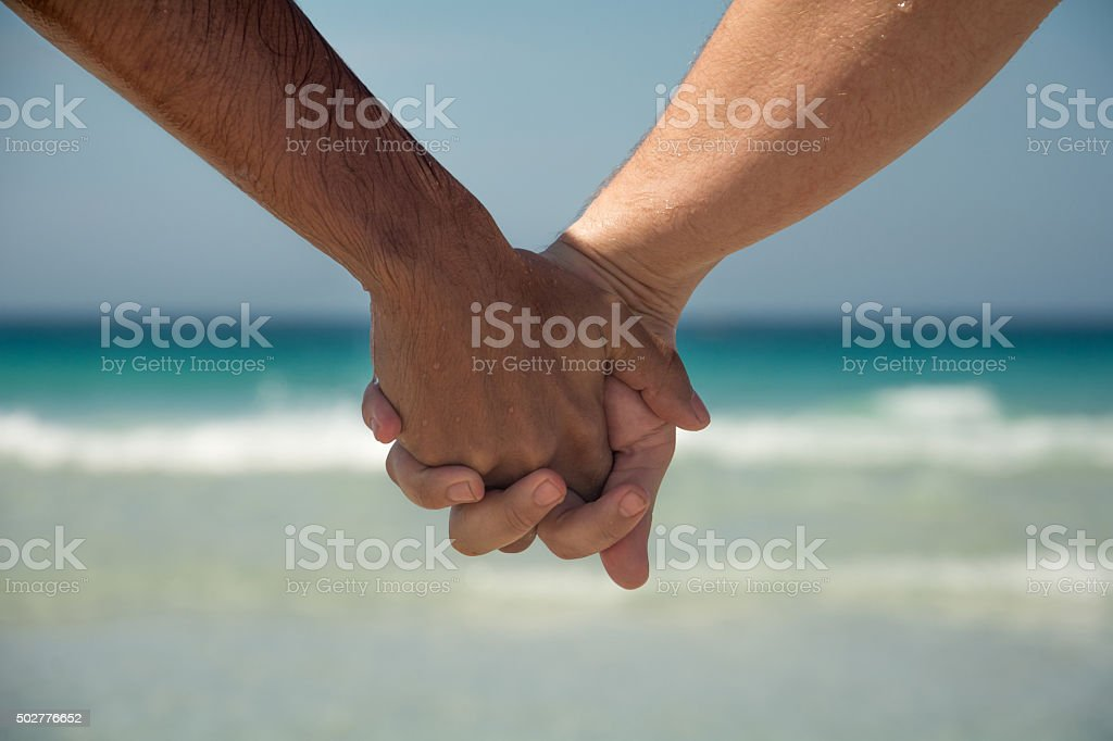 Hands together. Love couple - gay men - beach stock photo