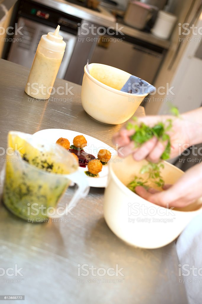 Hands Tossing Salad Greens in Kitchen stock photo