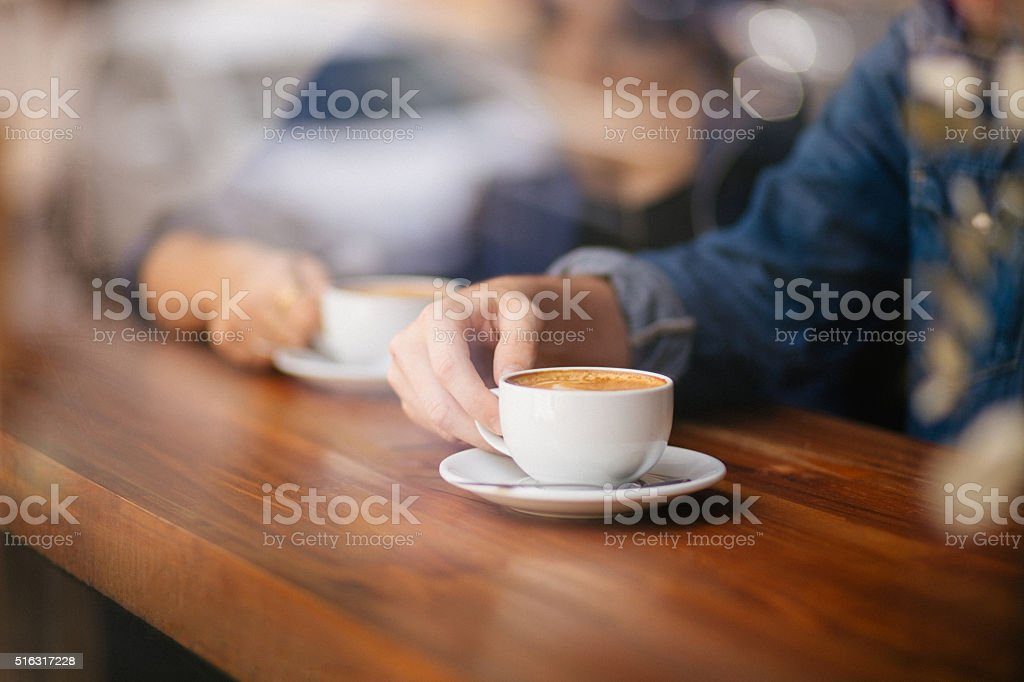 Hands Touching Coffee Cups on Cafe Counter stock photo