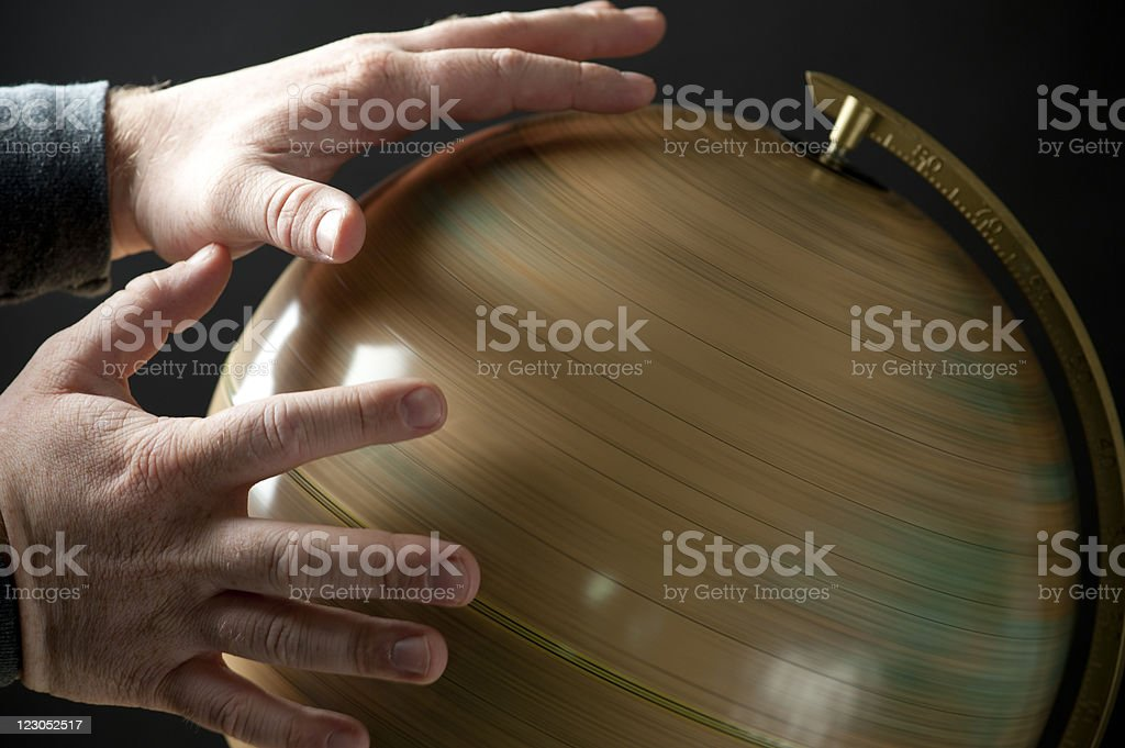 Hands Trying to Stop Spinning Globe stock photo