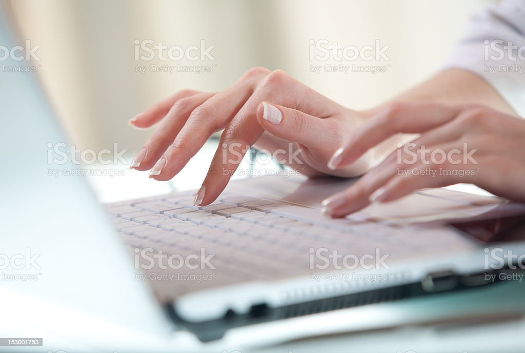 Hands typing on a laptop keyboard stock photo