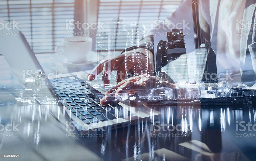 hands typing on laptop, double exposure stock photo