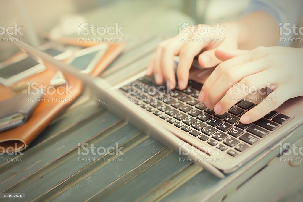 Hands typing on laptop - work anywhere concept (selective focus) stock photo