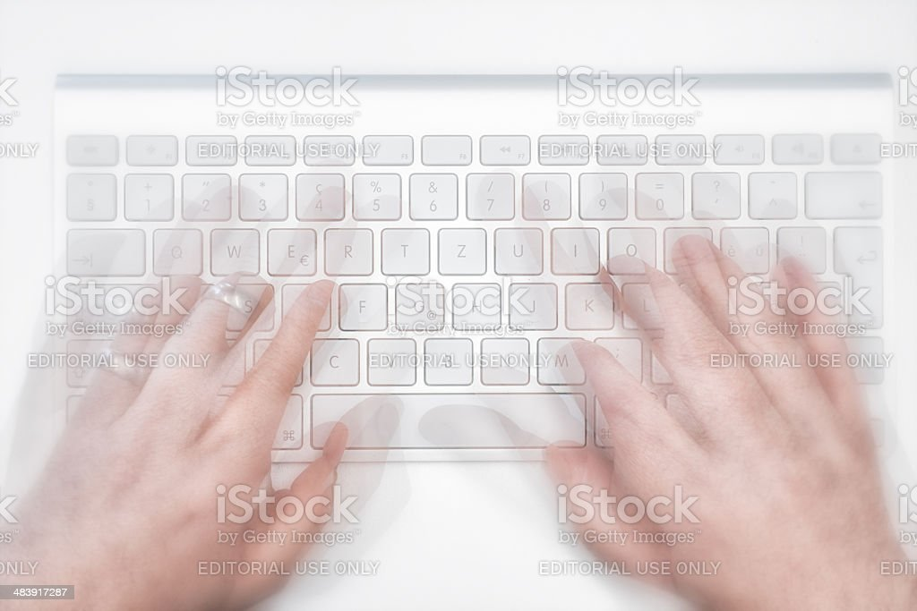 hands typing on new wireless mac apple keyboard royalty-free stock photo