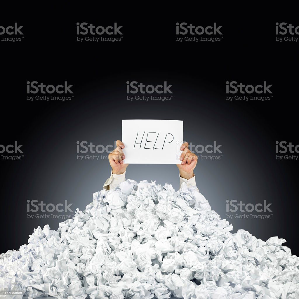 Hands under a pile of crumpled paper holding a help sign stock photo