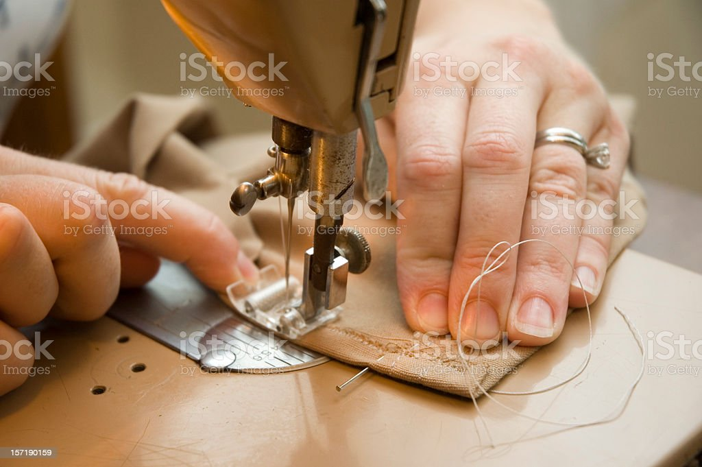 Hands using a sewing machine to sew brown material royalty-free stock photo