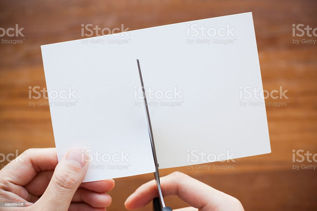 Hands Using Scissors Cutting a Blank Paper stock photo