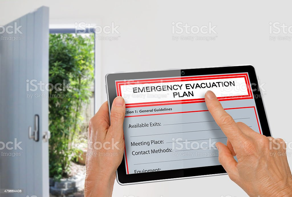 Hands using Tablet with Emergency Evacuation Plan beside Exit Door stock photo