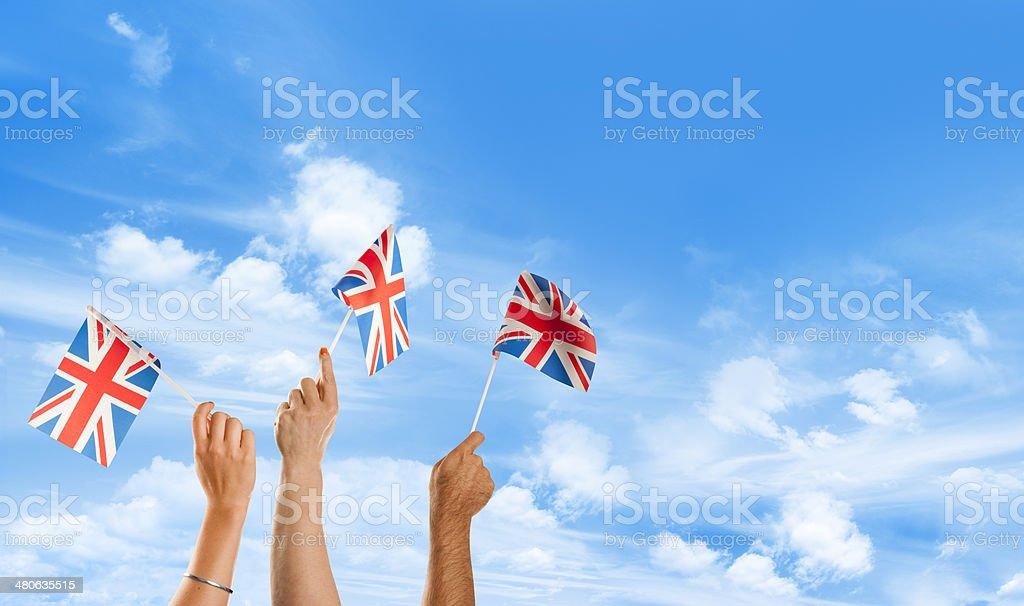 3 hands waving union jack flags against a blue sky royalty-free stock photo