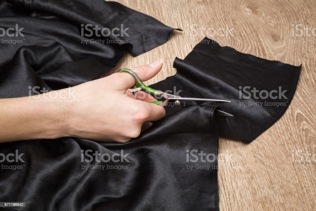 Hands with a scissors cuts a cloth. Sewing clothes. Handmade. Womanly hobby. stock photo