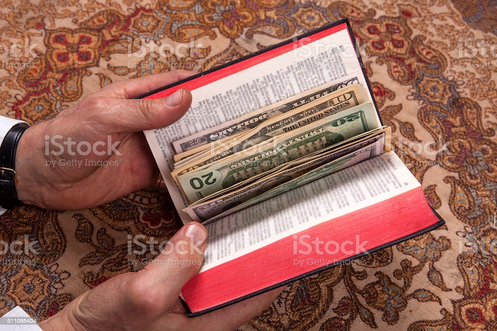 Hands With Bible and money stock photo