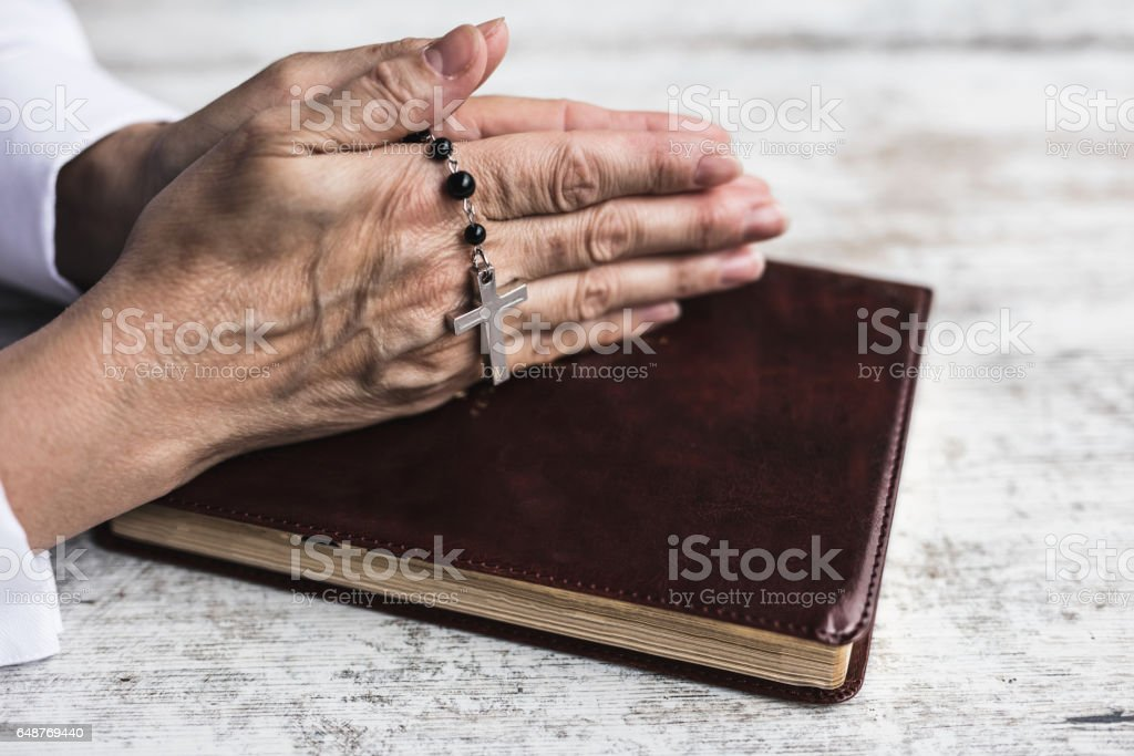 Hands with black rosary folded in prayer over old Holy Bible. Wooden background. stock photo