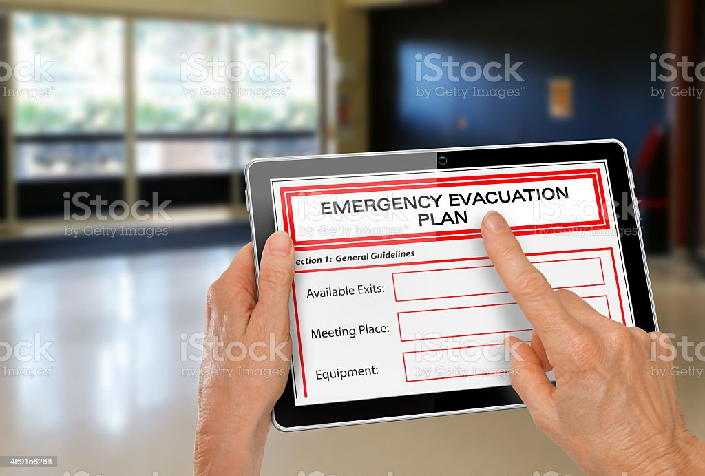 Hands with Computer Tablet and Emergency Evacuation Plan by Doors stock photo
