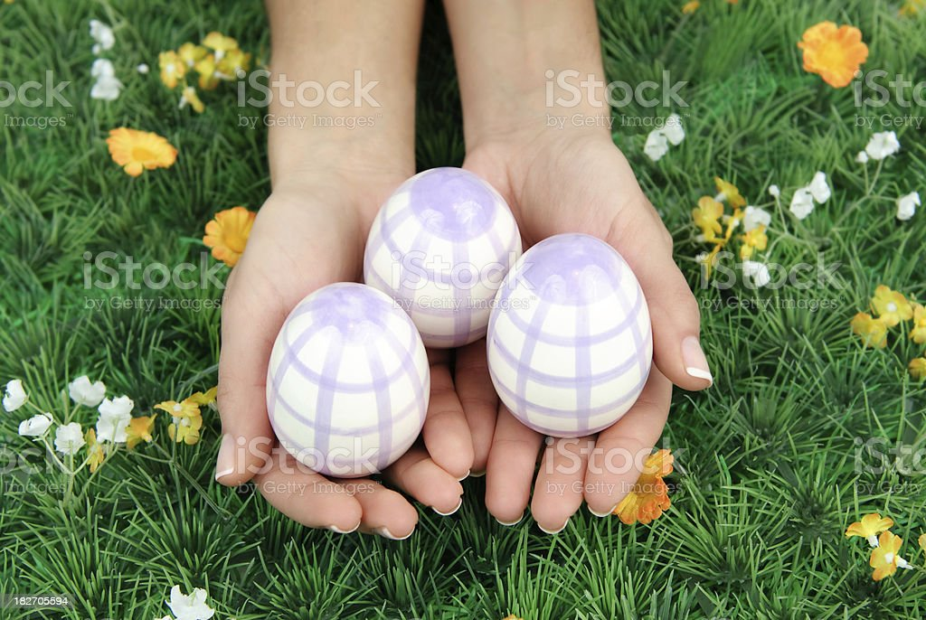 Hands with Easter eggs on grass stock photo